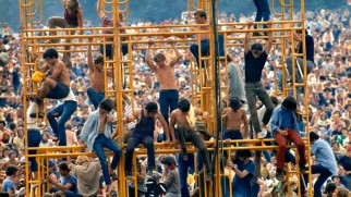 """Bethel, New York: August 1969. Crowd and people sitting on the sound tower. ©Elliott Landy / The Image Works NOTE: The copyright notice must include """"The Image Works"""" DO NOT SHORTEN THE NAME OF THE COMPANY"""